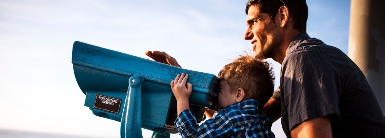 Vader ondersteunt zijn zoon die door een grote verrekijker kijkt