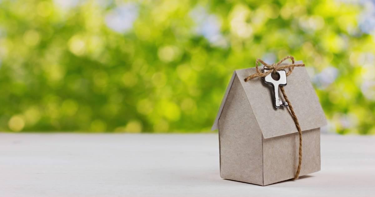 Een papieren huisje met een touwtje eromheen waar een sleutel aan vastzit