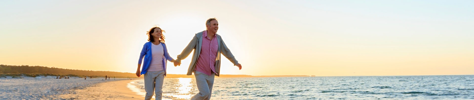 een oudere man en vrouw die over het strand rennen met de zon achter zich
